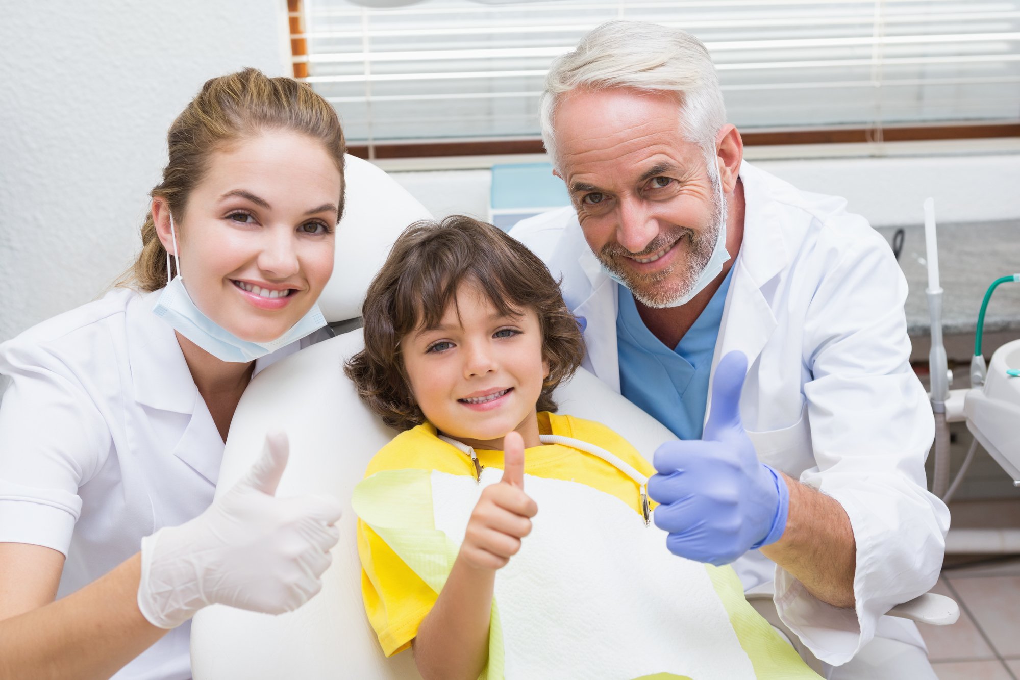 Pediatric dentist assistant and little boy all smiling at camera with thumbs up at the dental clinic